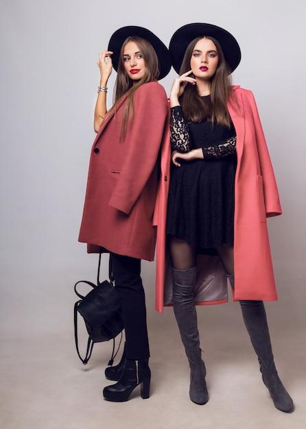Dwie Modne Młode Kobiety W Swobodnym Wiosennym Płaszczu, Botkach Na Obcasie, Czarnej Czapce I Stylowej Torebce Darmowe Zdjęcia