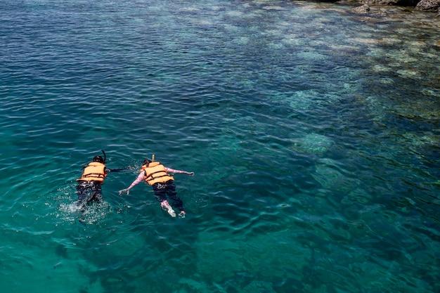Dwie Osoby Nurkujące Z Rurką Noszą Kamizelkę Ratunkową Na Rafie Koralowej Z Czystą, Błękitną Wodą Oceanu W Tropikalnym, Czystym Morzu Premium Zdjęcia