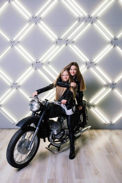 Dwie Piękne Dziewczyny Ubrane W Kostiumy Zawodników I Siedzące Na Motocyklu W Studio Premium Zdjęcia