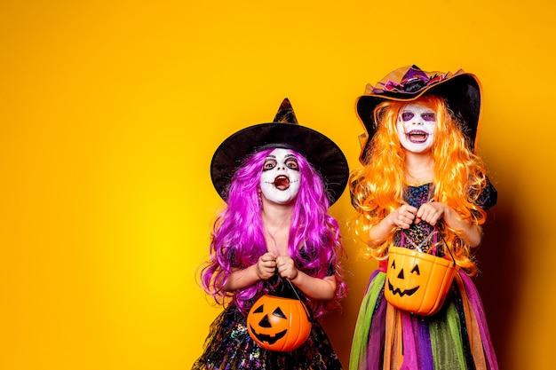 Dwie piękne dziewczyny w strojach czarownic straszą i robią miny Premium Zdjęcia