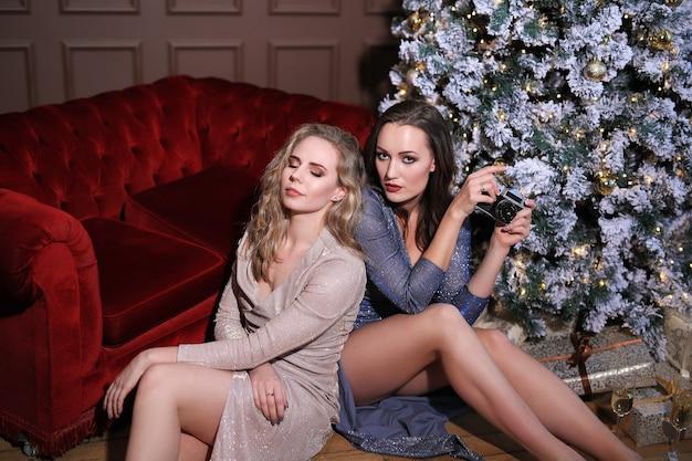 Dwie Piękne Kobiety świętują Boże Narodzenie Wraz Z Modną Sukienką. Boże Narodzenie W Domu Darmowe Zdjęcia