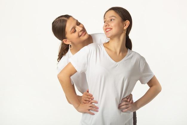 Dwie Piękne Młode Kobiety W Białych Koszulkach Na Białym Tle Premium Zdjęcia