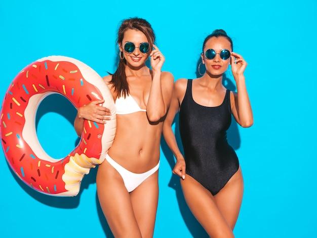 Dwie Piękne Seksowne Uśmiechnięte Kobiety W Białych I Czarnych Strojach Kąpielowych W Lecie. Dziewczyny W Okularach Przeciwsłonecznych. Pozytywne Modele Zabawy Z Dmuchanym Materacem Lilo Na Białym Tle Na Niebieskiej ścianie Darmowe Zdjęcia