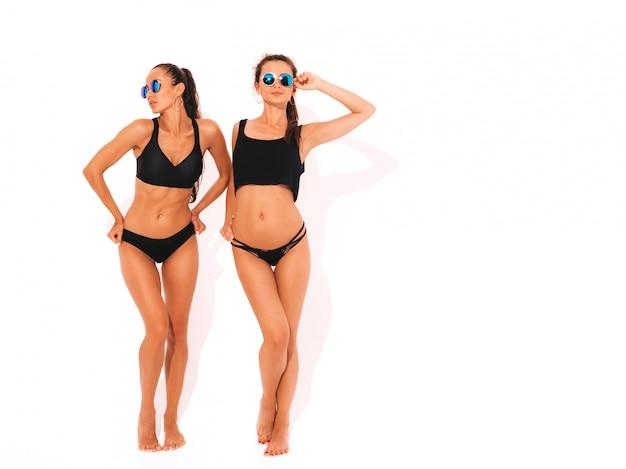 Dwie Piękne Seksowne Uśmiechnięte Kobiety W Czarnej Bieliźnie. Modne Gorące Modele Zabawy. Dziewczyny Na Białym Tle W Okularach Przeciwsłonecznych. Pełna Długość Darmowe Zdjęcia