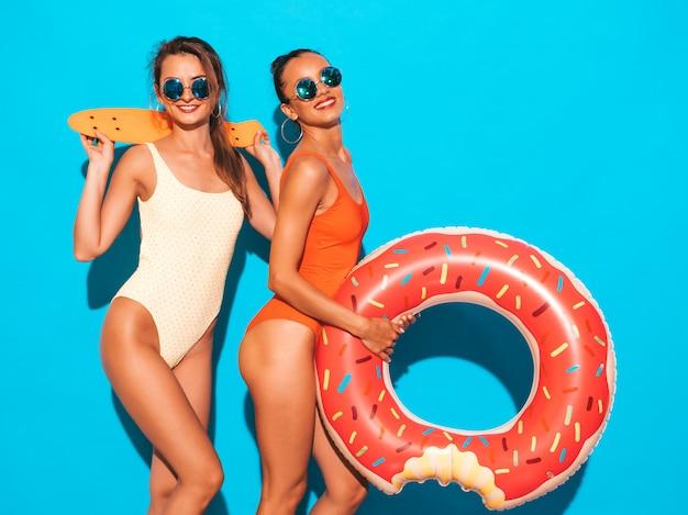 Dwie Piękne Seksowne Uśmiechnięte Kobiety W Kolorowe Kolorowe Stroje Kąpielowe Kostiumy Kąpielowe. Dziewczyny W Okularach Przeciwsłonecznych. Pozytywne Modele Zabawy Z Kolorowymi Deskorolkami Grosza. Z Dmuchanym Materacem Lilo Darmowe Zdjęcia