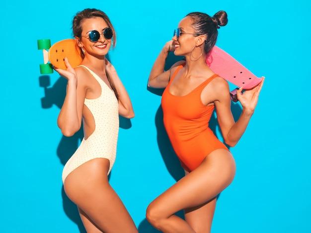 Dwie Piękne Seksowne Uśmiechnięte Kobiety W Kolorowe Kolorowe Stroje Kąpielowe Kostiumy Kąpielowe. Modne Dziewczyny W Okularach Przeciwsłonecznych. Pozytywne Modele Zabawy Z Kolorowymi Deskorolkami Grosza. Odosobniony Darmowe Zdjęcia