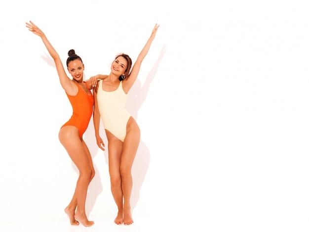 Dwie Piękne Seksowne Uśmiechnięte Kobiety W Kolorowe Kolorowe Stroje Kąpielowe W Czerwone I żółte Stroje Kąpielowe. Modne Gorące Modele Zabawy. Dziewczyny Na Białym Tle. Podnoszenie Rąk. Pełna Długość Darmowe Zdjęcia