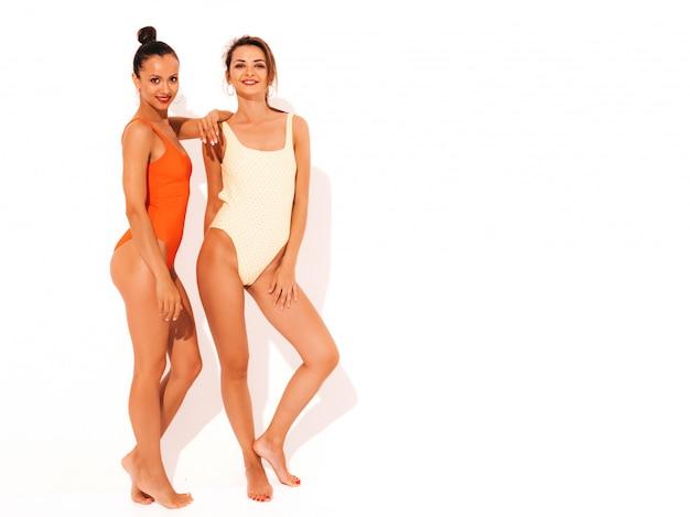 Dwie Piękne Seksowne Uśmiechnięte Kobiety W Kolorowe Kolorowe Stroje Kąpielowe W Czerwone I żółte Stroje Kąpielowe. Modne Gorące Modele Zabawy. Dziewczyny Na Białym Tle Darmowe Zdjęcia