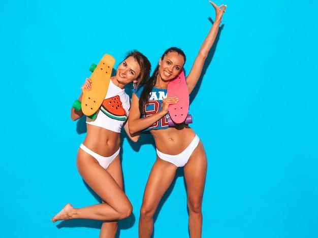 Dwie Piękne Uśmiechnięte Seksowne Kobiety W Letnich Majtkach I Temacie. Modne Dziewczyny. Pozytywne Modele Zabawy Z Kolorowymi Deskorolkami Grosza. Odosobniony. Podnoszenie Ręki Darmowe Zdjęcia