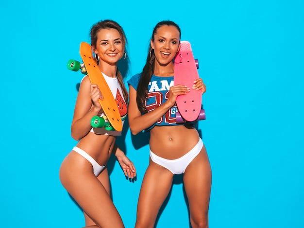 Dwie Piękne Uśmiechnięte Seksowne Kobiety W Letnich Majtkach I Temacie. Modne Dziewczyny. Pozytywne Modele Zabawy Z Kolorowymi Deskorolkami Grosza. Odosobniony Darmowe Zdjęcia