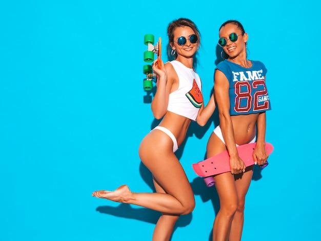 Dwie Piękne Uśmiechnięte Seksowne Kobiety W Letnich Majtkach I Temacie. Modne Dziewczyny W Okularach Przeciwsłonecznych. Pozytywne Modele Zabawy Z Kolorowymi Deskorolkami Grosza. Odosobniony Darmowe Zdjęcia