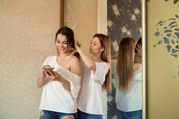 Dwie piękne uśmiechnięte siostry lub koleżanki idą na imprezę i robią sobie fryzury w domu. Premium Zdjęcia