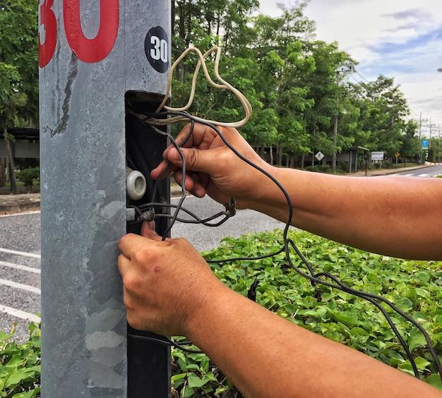 Dwie Ręce Elektryka Naprawy Drutu Elektrycznego W Słupie Lampy. Premium Zdjęcia