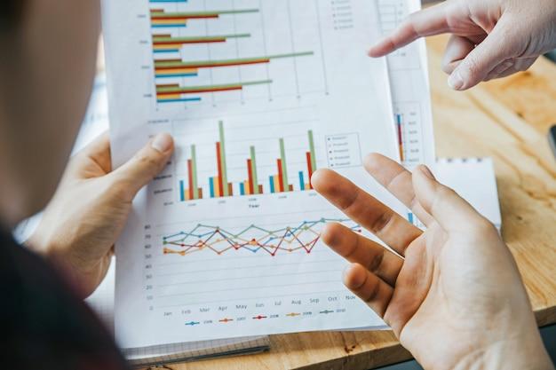 Dwie ręce młodych biznesmenów analizują wykresy inwestycyjne. Premium Zdjęcia
