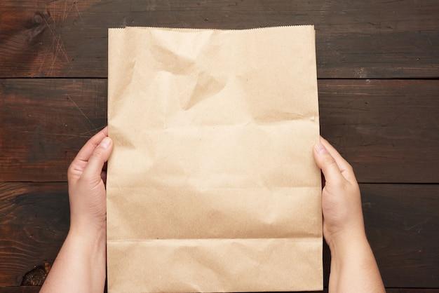 Dwie Ręce Trzyma Papierową Torbę Brązowego Papieru Kraftowego Nad Drewnianym Stołem Premium Zdjęcia