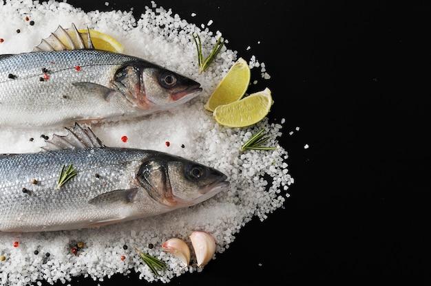 Dwie ryby morskie w soli z cytryną, limonką, rozmarynem i przyprawami Premium Zdjęcia