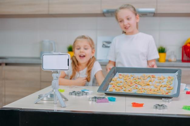 Dwie Siostry Blogerki Robią Ciasteczka I Nagrywają Filmy Szkoleniowe Na Smartfonie. Premium Zdjęcia