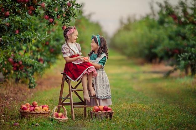 Dwie śliczne Siostry W Stylu Vintage W Sadzie Jabłkowym śmieją Się I Baw Się Dobrze Premium Zdjęcia