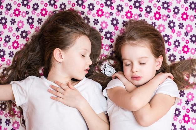 Dwie śpiące dziewczynki i biały budzik Premium Zdjęcia