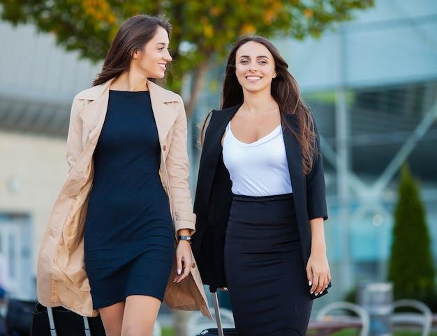 Dwie szczęśliwe dziewczyny podróżujące razem za granicę, niosące bagaż walizki na lotnisku Premium Zdjęcia