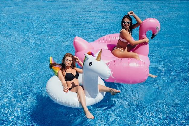 Dwie Szczęśliwe Dziewczyny Z Pięknymi Postaciami Na Nadmuchiwanych Flamingach I Jednorożcach W Basenie Premium Zdjęcia