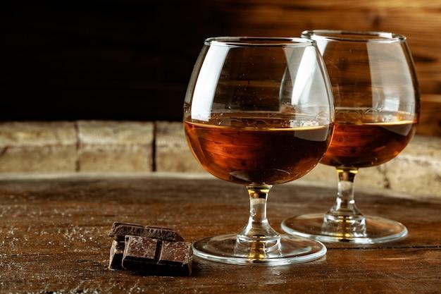 Dwie Szklanki Bourbonu Lub Szkockiej Lub Brandy I Kawałków Gorzkiej Czekolady Premium Zdjęcia