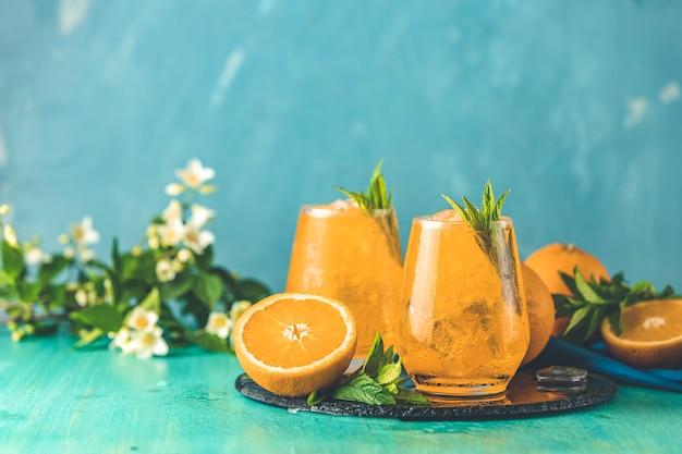 Dwie Szklanki Pomarańczowego Lodu Piją Ze świeżą Miętą Na Drewnianej Powierzchni Stołu Turkusowego Premium Zdjęcia