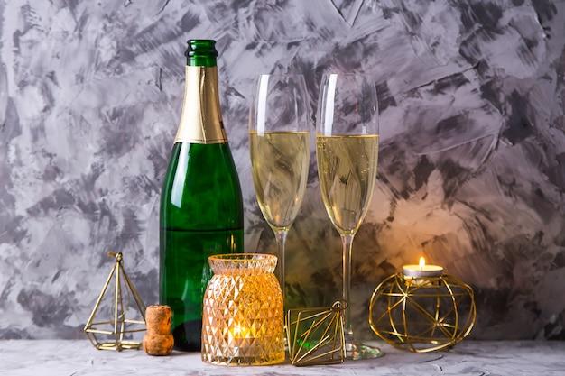 Dwie szklanki szampana obok butelki i złotym kolorze dekoracji świątecznej Premium Zdjęcia