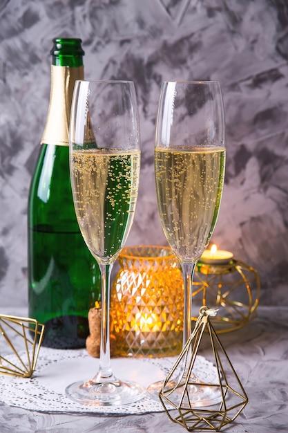 Dwie szklanki szampana obok butelki Premium Zdjęcia