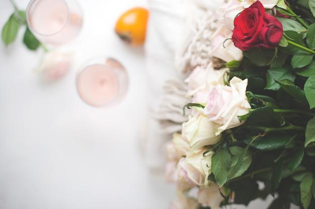 Dwie Szklanki Wina I Duży Bukiet Róż W Domu Przy Oknie. Wolne Miejsce Na Tekst. Premium Zdjęcia