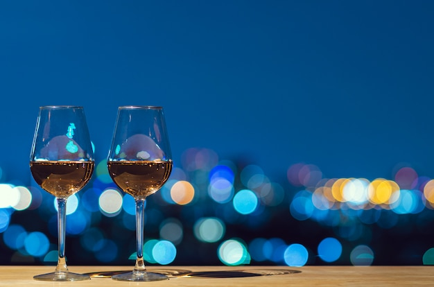 Dwie szklanki wina różanego z kolorowym światłem bokeh miasta z budynku na dachu. Premium Zdjęcia