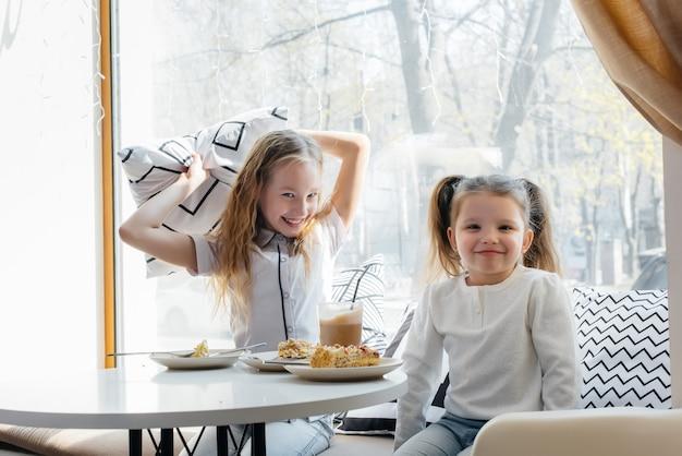 Dwie Urocze Dziewczynki Siedzą W Kawiarni I Bawią Się W Słoneczny Dzień. Rekreacja I Styl życia. Premium Zdjęcia