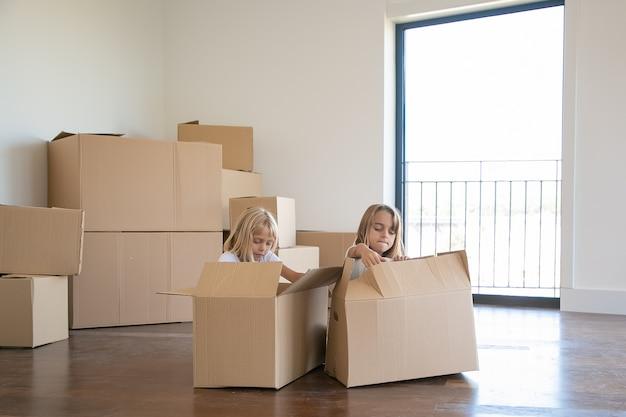 Dwie Urocze Dziewczyny Rozpakowują Rzeczy W Nowym Mieszkaniu, Siedzą Na Podłodze Obok Otwartych Pudełek Z Kreskówkami Darmowe Zdjęcia