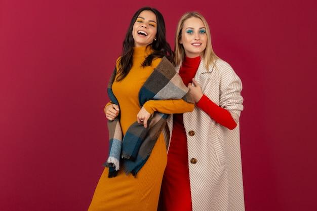 Dwie Uśmiechnięte Atrakcyjne Stylowe Kobiety W Jesień Zima Moda Sukienka I Płaszcz Pozowanie Na Białym Tle Na Czerwonej ścianie Darmowe Zdjęcia