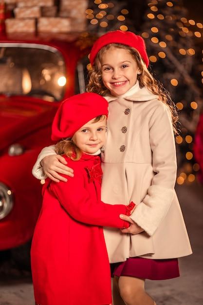 Dwie Zabawne Dziewczyny Na Ulicy W śnieżną Pogodę Czerwonym Samochodem W Oczekiwaniu Na Nowy Rok Premium Zdjęcia