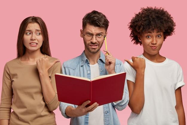 Dwie Zawstydzone Kobiety Innej Rasy Wskazują Na Zaintrygowanego Faceta, Proponują Zadać Mu To Pytanie, Ponieważ Nie Znają Odpowiedzi, Stoją Razem Pod Różową ścianą. Motyw Edukacyjny Darmowe Zdjęcia