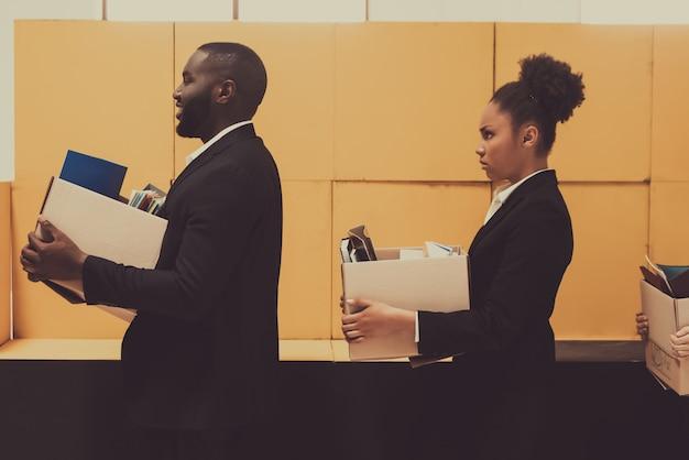 Dwóch afroamerykańskich menedżerów z pudełkami biurowymi. Premium Zdjęcia