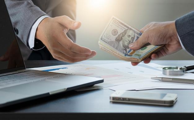 Dwóch Biznesmenów Daje I Bierze Banknot Dolara Amerykańskiego. Premium Zdjęcia