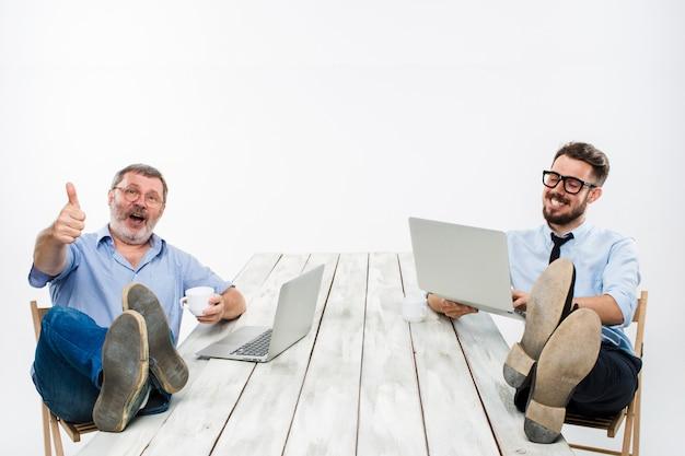 Dwóch Biznesmenów Z Nogami Nad Stołem Pracujących Na Laptopach Darmowe Zdjęcia