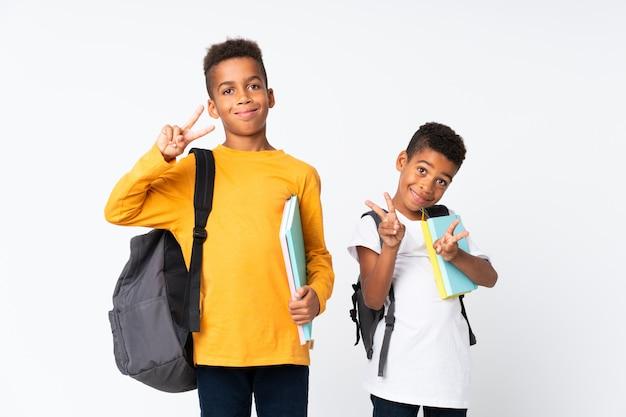 Dwóch chłopców afroamerykanów studentów nad białym i gest zwycięstwa Premium Zdjęcia
