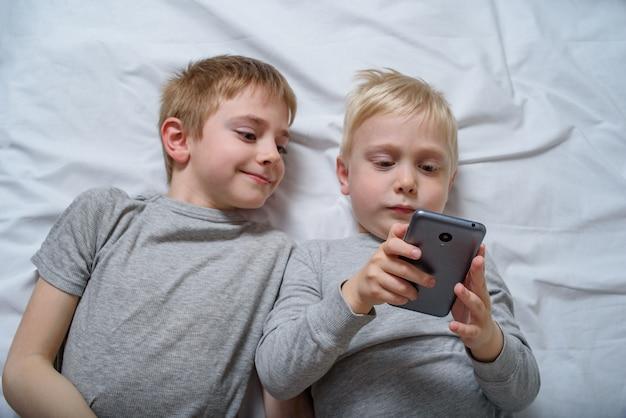 Dwóch chłopców leży w łóżku ze smartfonem. gadżet wypoczynek Premium Zdjęcia
