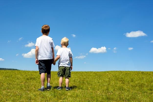 Dwóch chłopców stojących na łące, trzymając się za ręce Premium Zdjęcia