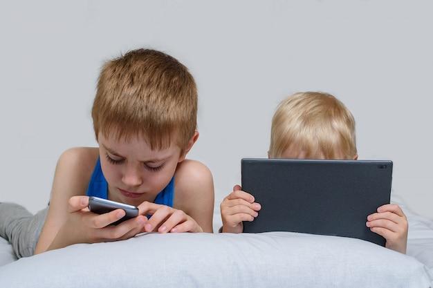 Dwóch Chłopców Z Gadżetami Leży W łóżku. Dzieci Korzystają Ze Smartfona I Tabletu Premium Zdjęcia