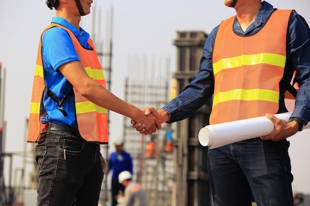Dwóch Inżynierów Budowlanych Uścisnąć Dłoń Na Placu Budowy Premium Zdjęcia