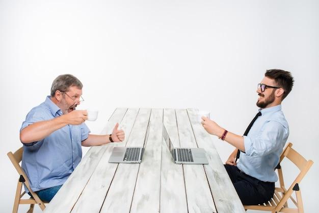 Dwóch Kolegów Pracujących Razem Nad Projektem Na Jasnoszarym Tle. Piją Kawę. Szczęśliwy Człowiek I Zazdrosny Człowiek. Pojęcie Konkurencji W Biznesie Darmowe Zdjęcia