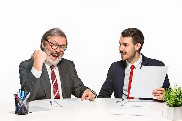 Dwóch Kolegów Pracujących Razem W Biurze Na Białym Tle. Darmowe Zdjęcia