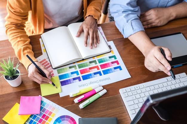 Dwóch kreatywnych grafików pracujących przy wyborze kolorów i próbkach kolorów, rysujących na tablecie graficznym Premium Zdjęcia