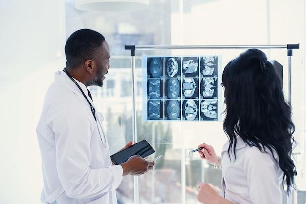 Dwóch Lekarzy Patrzy Na Zdjęcia Rentgenowskie. Medyczny. Widok Z Tyłu Głównego Lekarza Afro Amerykańskiego Mężczyzny I Kobiety Rasy Kaukaskiej, Patrząc Na Zdjęcia Rentgenowskie Mri W Czystym świetle Premium Zdjęcia