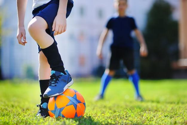Dwóch małych chłopców zabawy gra mecz piłki nożnej w słoneczny letni dzień Premium Zdjęcia
