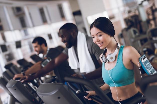 Dwóch mężczyzn i kobieta uśmiechając się ćwiczyć na bieżniach. Premium Zdjęcia